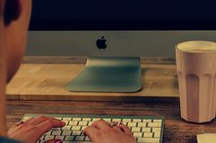 Person Typing on Apple Brand Wireless Keyboard Stock Photo