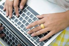Person Typing en un ordenador portátil moderno en parque Foto de archivo