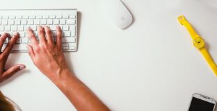 Person typing on keyboard at desk Royalty Free Stock Images