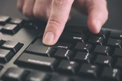 Person typing on a keyboard and pressing Enter key royalty free stock image