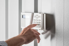 Person typing on keypad of home security alarm. Security system concept Royalty Free Stock Photo