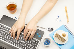 Person is typing on the laptop keyboard on your workspace. Stock Photo