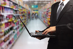 Person typing on laptop in supermarket in blurry Stock Photography