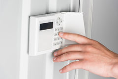 Person typing password on home security alarm, security system concept Stock Images