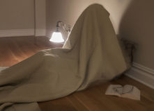 Person under blanket in empty room Royalty Free Stock Photo