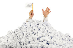 Person under crumpled pile of papers. With hand holding a help sign / isolated on white Royalty Free Stock Photography