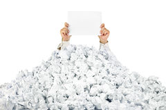 Person under crumpled pile of papers with a blank. Person under crumpled pile of papers with hand holding a blank page /  on white Royalty Free Stock Image