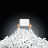 Person under crumpled pile of papers with help si. Person under crumpled pile of papers with hand holding a help sign Stock Photo