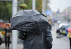 The person under an umbrella. The person in rainy weather hides under the broken umbrella Stock Images
