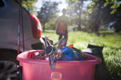 Person unloading car on camping trip in woodland clearing, focus on camping stove in pink container (backlit) Stock Photography
