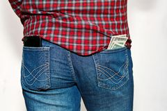 Person with unsafe stick out from pocket money. Male person in work outfit - checkered shirt and classic jeans. Cell phone and stack of US dollars currency Royalty Free Stock Photos