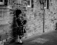 Person Using Bagpipes Near Wall in Grayscale Photography Royalty Free Stock Images