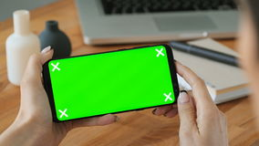 Person using cell phone with green screen display in hand. And woman make a gesture. Closeup concept of copy space advertising for app. Portable gadget with stock video footage