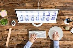 Person Using Computer With Calendar na tela fotos de stock