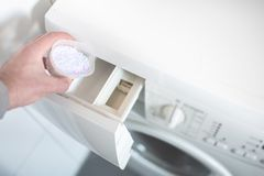 Person using dosing aid to pout laundry detergent powder into washing machine stock image