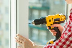 Person using drill on window. Person using power drill installing windows. Working at flat remodeling. Building, repair and renovation stock photo