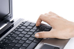 Person using laptop computer. Hand of person typing on open laptop computer pressing enter button, white background Stock Photo