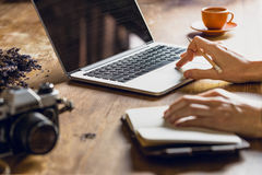 Person using laptop and diary at workspace with vintage camera Royalty Free Stock Photo