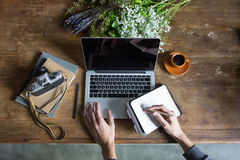 Person using laptop and graphic tablet at workspace with notebooks and camera. Person using laptop and graphic tablet at workspace with notebooks and vintage Royalty Free Stock Photography