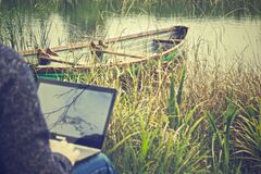 Person using laptop by lake