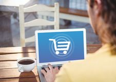 Person using Laptop with Shopping trolley icon Royalty Free Stock Image
