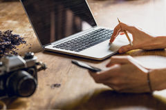 Person using laptop and smartphone at workspace with vintage camera. Person using laptop and smartphone at workspace with vintage photo camera royalty free stock photography