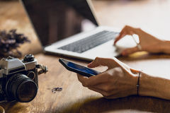 Person using laptop and smartphone at workspace with vintage camera. Person using laptop and smartphone at workspace with vintage photo camera stock photo
