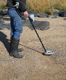 Person using metal detector. On beach looking for treasure royalty free stock photo