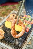 Turning sausage on grill. Person using metal tongs to turn sausage on grill royalty free stock photo