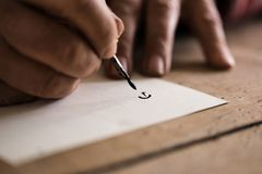 Person using a nib pen and ink to do calligraphy. In a close up view of his hands and the first letter drawn on the paper Royalty Free Stock Image