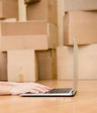 Person using notebook with cardboard boxes on background Stock Images