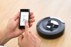 Person using remote control of robotic vacuum cleaner Stock Images