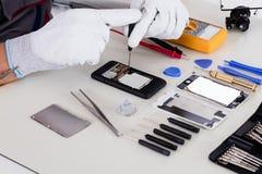 Person Using Screwdriver To Repair Gebroken Telefoon royalty-vrije stock afbeelding