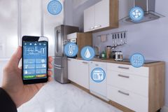 Person Using Smart Home Application On Smartphone. Close-up Of A Person`s Hand Using Smart Home Application On Smartphone In Kitchen stock image