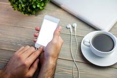 Person using smart next to coffee mug at desk. Cropped image of person using smart next to coffee mug at desk Royalty Free Stock Image