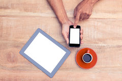 Person using smart phone by coffee and tablet on table Stock Images