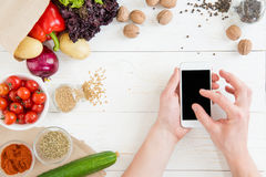 Person using smartphone with blank screen while cooking and fresh ingredients on wooden table Stock Photo
