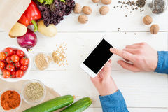 Person using smartphone with blank screen while cooking and fresh ingredients on wooden table Stock Image