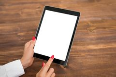 Person using tablet with empty blank screen, vertical orientation. Woman holding tablet on wooden table Stock Images