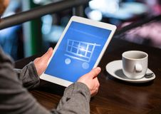 Person using Tablet with Shopping trolley icon and coffee Stock Photography