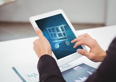 Person using Tablet with Shopping trolley icon Stock Photography
