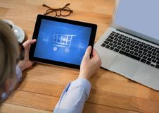 Person using Tablet with Shopping trolley icon Royalty Free Stock Photography
