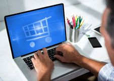 Person using Tablet with Shopping trolley icon Royalty Free Stock Photo