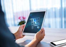 Person using Tablet with Shopping trolley icon Stock Images