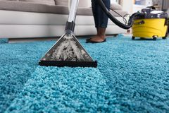 Person Using Vacuum Cleaner For Cleaning Carpet. Person Using Vacuum Cleaner For Cleaning Blue Carpet At Home royalty free stock images