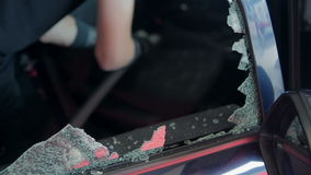 Person is vacuuming broken window from inside of a car stock footage