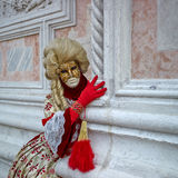 Person in Venetian costume attends Carnival of Venice. Stock Photos