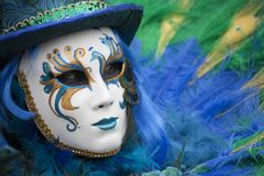 Person at Venice Carnival dressed in a blue, yellow & green venetian costume and venetian mask with a feather Venice Italy royalty free stock image