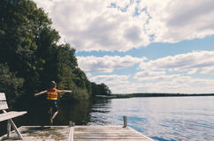 Person With a Vest Jumping on the Lake Under Cloudy Sky Royalty Free Stock Photos