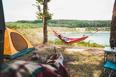 Free Person View Couple Resting At Camping Woman Laying In Hammock With Beautiful View Of Forest Lake Royalty Free Stock Images - 182109359